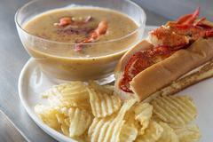 Lobster soup with a lobster roll and potato crisps Stock Photos