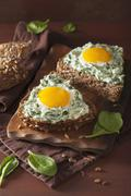 A sunflower seed roll topped with spinach cream cheese and fried eggs Stock Photos