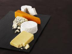 A selection of cheeses on a black platter Stock Photos