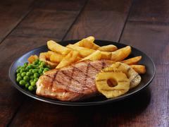 Ham steak with pineapple and chips Stock Photos