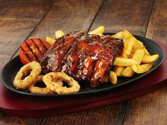 Glazed ribs with chips and onion rings Stock Photos