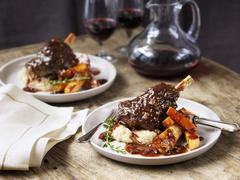 Lamb shanks with mashed potatoes, parsnips, gravy and wine Stock Photos