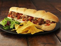 A meatball sub with cheese and crisps Stock Photos