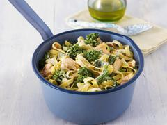 Tagliatelle with salmon, spinach and broccoli in a saucepan Stock Photos