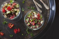 Salad with red quinoa, tomatoes, cucumber, feta cheese and mint Stock Photos