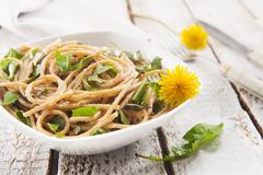 Wholemeal spaghetti with dandelions and ricotta Stock Photos