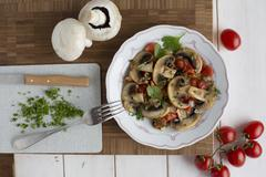 Fried mushrooms and tomatoes with coriander Stock Photos