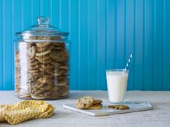 A giant cookie jar filled with chocolate chip cookies with a plate of cookies Stock Photos