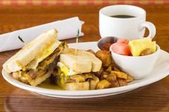 A breakfast sandwich with fried potatoes, fruit salad and coffee Stock Photos