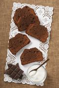 Slices of chocolate cake, sugar and pieces of chocolate on a doily Stock Photos