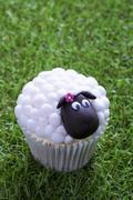 An Easter lamb cupcake on a grass surface Stock Photos