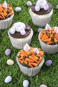 Various Easter cupcakes on a grass surface Stock Photos