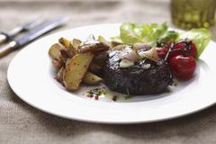 Rump steak with potato wedges and cherry tomatoes Stock Photos