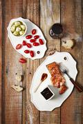 An anti pasti platter with salmon, tomatoes, artichokes, bread and red wine Stock Photos