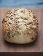 A loaf of country bread with seeds on a wooden board Stock Photos