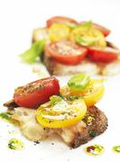 Bruschetta topped with red and yellow tomatoes Stock Photos