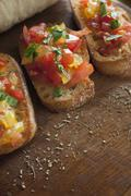 Bruschetta topped with basil and seasonings on a wooden surface Stock Photos