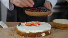 Woman cooking cake and decorating biscuit with berries Stock Footage