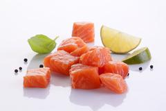 Diced fresh salmon, a basil leaf, peppercorns and lime wedges Stock Photos