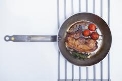 Fried beefsteak with cherry tomatoes and rosemary in a pan (seen from above) Stock Photos