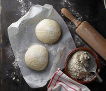 Two balls of pizza dough on a piece of paper with flour and a rolling pin Stock Photos
