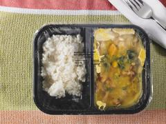 Pre-cooked and frozen chicken curry as a ready meal in a segregated plastic Stock Photos
