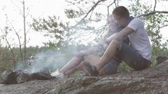 Happy teenager couple fried sausages on smoky bonfire in the forest Stock Footage