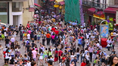 CROWDS OF PEOPLE ON COBBLED R DE SAO PAULO MACAU Stock Footage
