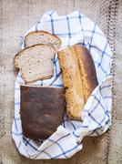 Two loaves of homemade sourdough rye bread on a checked tea towel Stock Photos