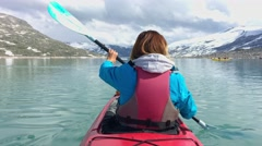 Woman kayaking on Styggvatnet glacier lake near Jostedalsbreen glacier Stock Footage