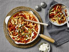 Pasta with tomato sauce, spicy sausage and feta cheese Stock Photos