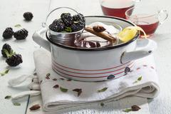 Glass cups of mulled wine, ingredients and cooking utensils Stock Photos
