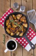 Spiced baked potatoes with rosemary in a cast iron pan Stock Photos