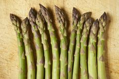 A row of green asparagus spears on a wooden board Stock Photos