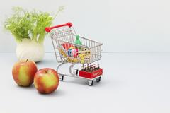 A mini shopping trolley filled with toy foodstuffs next to apples and a bulb of Stock Photos