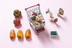 A mini shopping trolley filled with toy foodstuffs next to fresh vegetables and Stock Photos