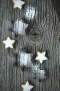 Star-shaped cutters with icing sugar and cinnamon stars on a wooden board Stock Photos