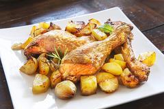 Roast chicken with potatoes, garlic and rosemary Stock Photos