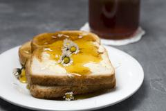 Slices of toast with honey and daises Stock Photos