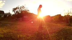 Long haired bearded men doing acrobatic jump kip up kick up on a summer sunset Stock Footage