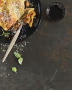 A portion of lasagne and a glass of red wine Stock Photos