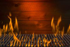 A flaming hot barbecue grill against a wooden wall Stock Photos