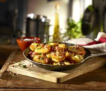 Fried potatoes with bacon and rosemary in a rustic pan Stock Photos