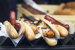 Hot dogs and grilled chicken skewers on a metal stand in a fast food shop Stock Photos