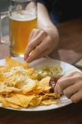 People eating nachos with cheese and two dips Stock Photos