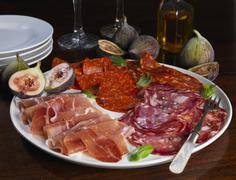 A platter of cold cuts with figs and basil Stock Photos