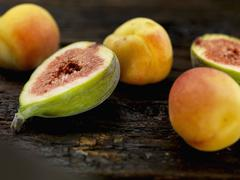 Figs and apricots on a wooden surface Stock Photos