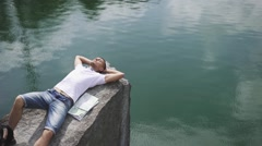 Young active man relaxes by resting on rock near calm mountain lake surface with Stock Footage