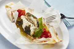 Cod cooked in parchment paper with tomatoes and herbs Stock Photos