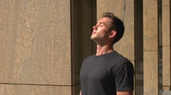 Close-up of young handsome man enjoying the sun in the city Stock Footage